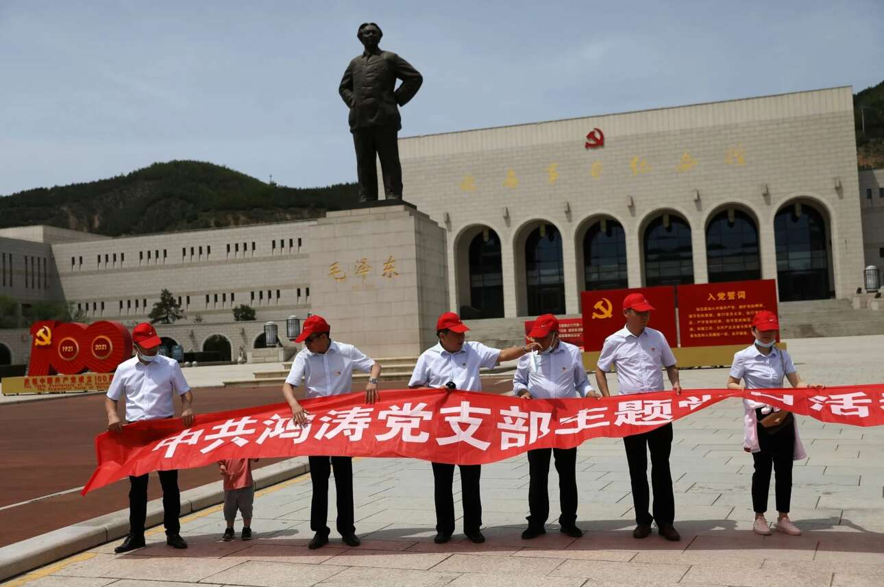 Μέλη του ΚΚΚ ανοίγουν πανό για τα 100 χρόνια του κόμματος μπροστά από το Μνημείο της Επανάστασης στο Γιανάν, απ' όπου λέγεται ότι ξεκίνησαν όλα. Πίσω τους, πάνω στο βάθρο του, ο Μάο ατενίζει τον 21ο αιώνα σαν νέος