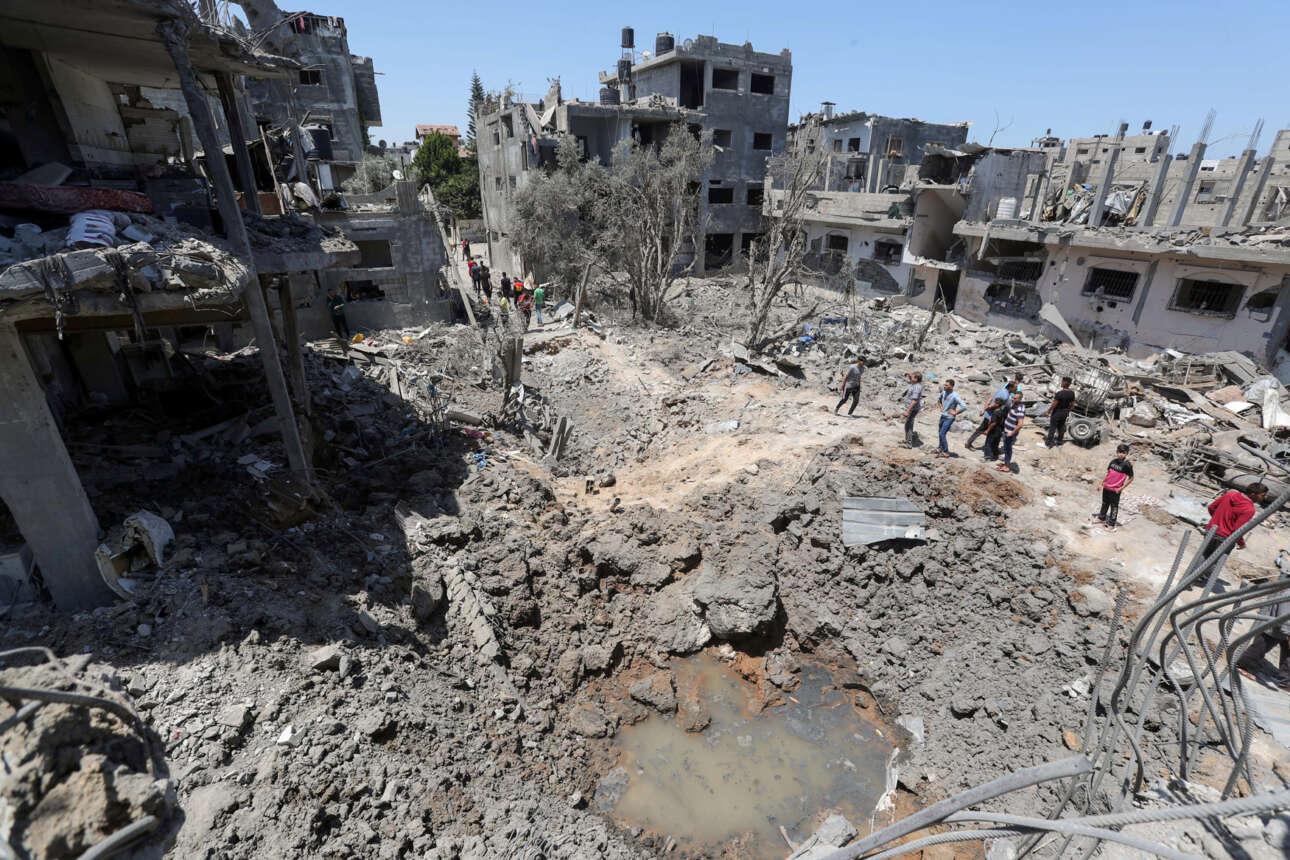 Παλαιστίνιοι βόρειας περιοχής της Λωρίδας της Γάζας κοιτάζουν τα χαλάσματα των κτιρίων που βομβάρδισαν οι Ισραηλινοί το προηγούμενο βράδυ