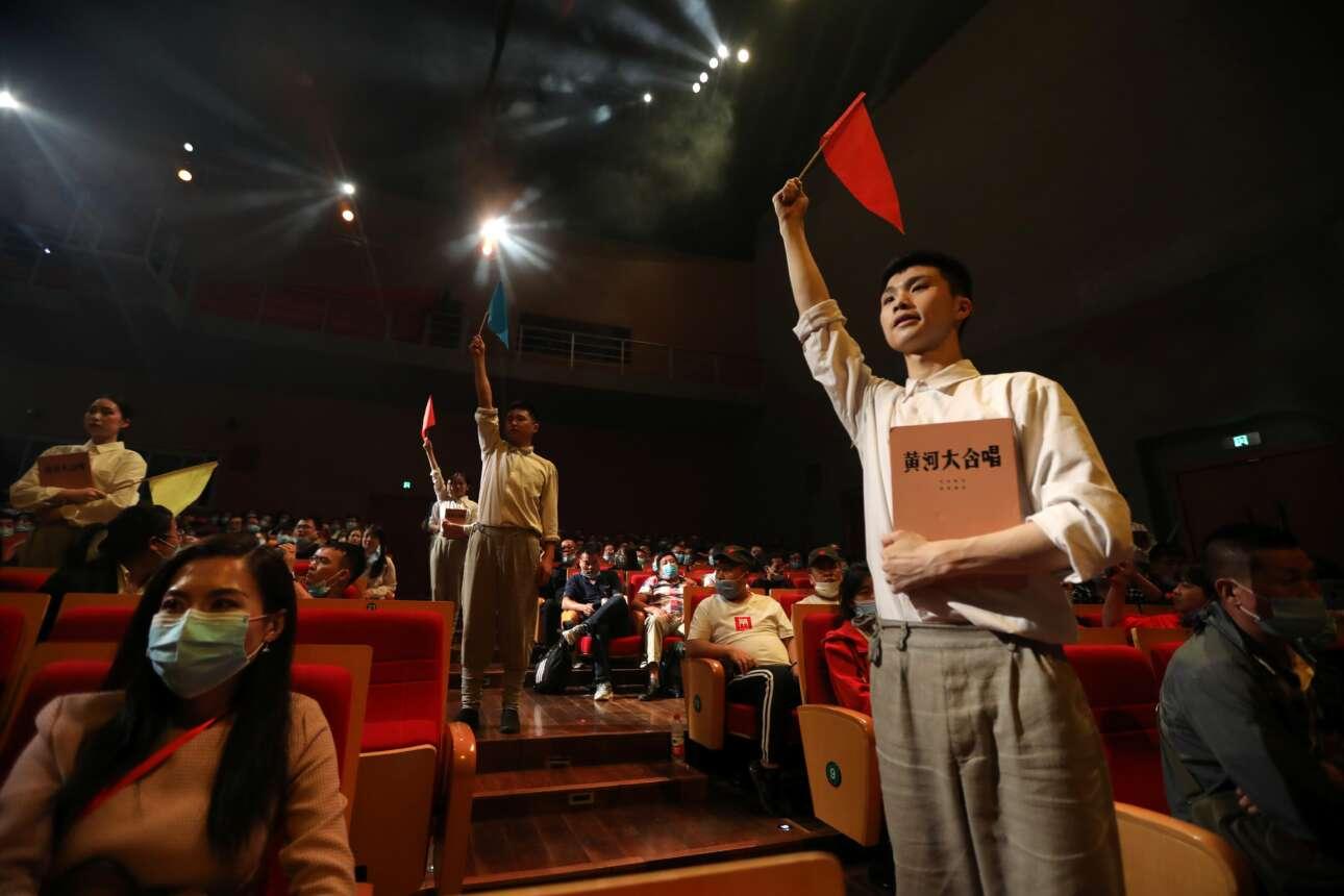Ας μη σκιαχτεί κανείς: οι νέοι με τα κόκκινα σημαιάκια δεν είναι ερυθροφρουροί, αλλά ηθοποιοί – παίζουν κάτι από την επαναστατική ιστορία της Κίνας σε θέατρο του Γιανάν, κατόπιν εντολής του κράτους