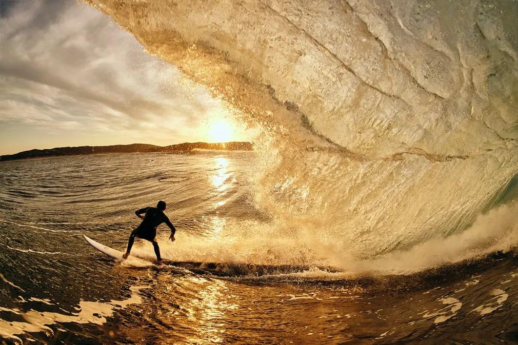 «Χρυσή Ώρα». Το κύμα μέσα στο οποίο κινείται ο σέρφερ μοιάζει πραγματικά χρυσαφένιο στη δημοφιλή για σέρφινγκ παραλία της κωμόπολης Μάργκαρετ Ρίβερ, νότια του Περθ, στην δυτική Αυστραλία.
