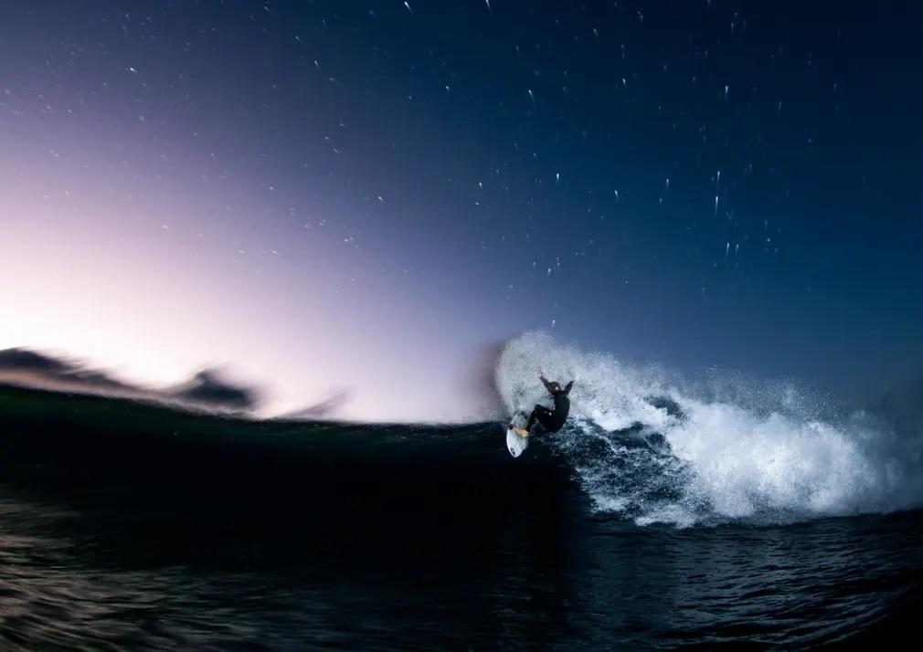 «Πορφυρή Βροχή». Σέρφινγκ κάτω από τις σταγόνες του νερού που εκτοξεύονται καθώς η σανίδα ακροβατεί πάνω στα κύματα