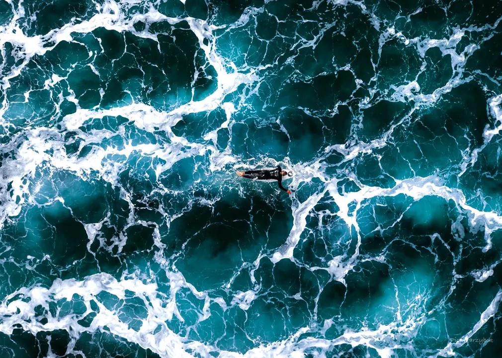 «Ηλεκτρική». Ο σέρφερ κολυμπά με την σανίδα του πάνω σε μια «κομματιασμένη» από τα ρεύματα και τα κύματα θάλασσα στην μεγαλύτερη παραλία του νησιού Stradbroke στην Αυστραλία. Η θάλασσα μοιάζει σαν έχει υποστεί… ηλεκτροπληξία