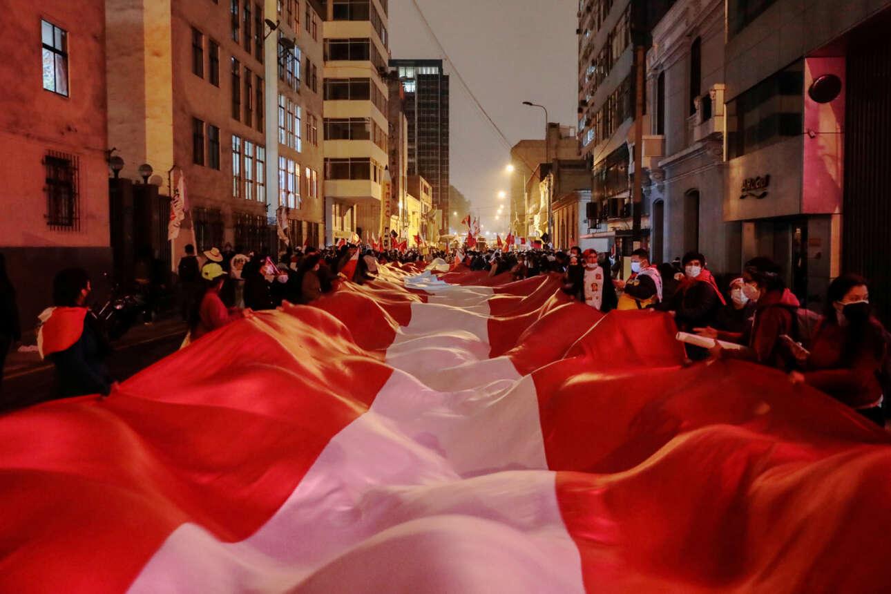 Οπαδοί του προεδρικού υποψηφίου Πέδρο Καστίγιο περιφέρονται στη Λίμα κρατώντας ένα τεραστίων διαστάσεων πανί στα εθνικά χρώματα του Περού