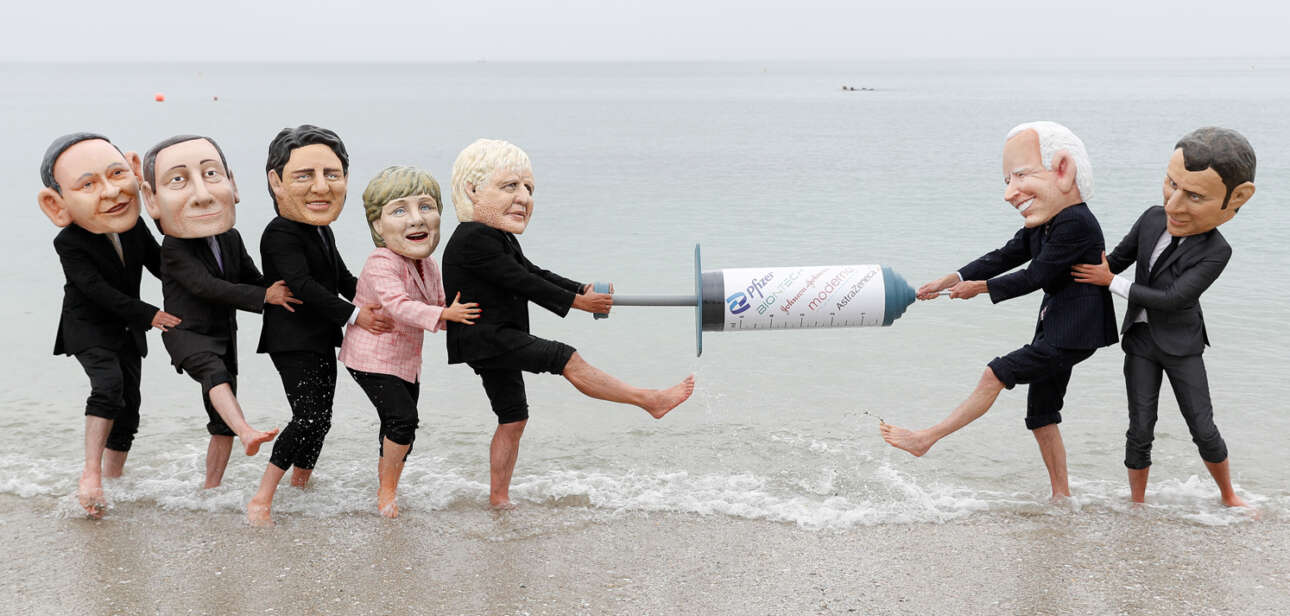 Βρετανικό χιούμορ: διελκυστίνδα ακτιβιστών γύρω από το εμβόλιο. Από δεξιά, από τη βελόνα, υποτίθεται ότι τραβούν οι Μπάιντεν και Μακρόν. Από αριστερά οι Τζόνσον, Μέρκελ, Τριντό (Καναδάς), Ντράγκι και Σούγκα (Ιαπωνία)