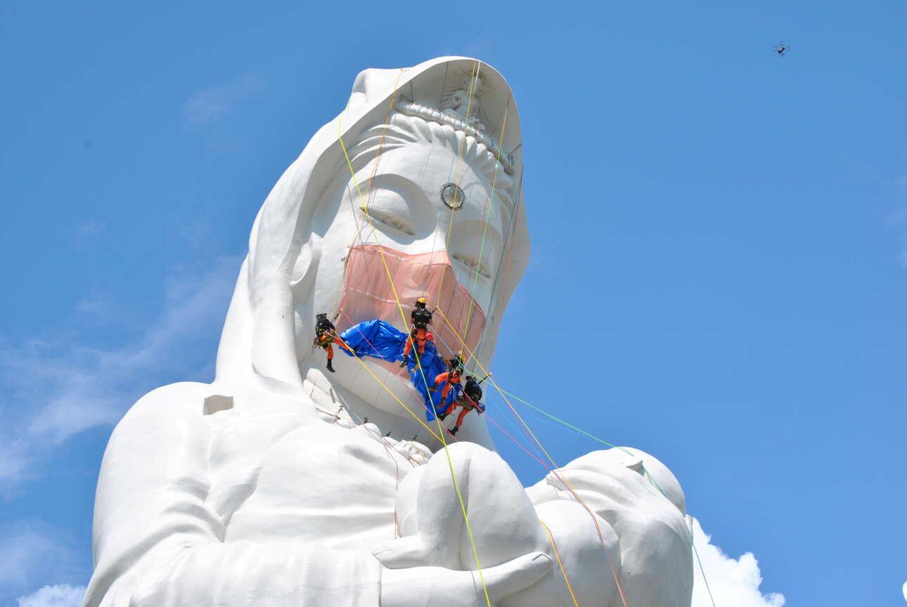 Εργάτες σκεπάζουν με πανί το στόμα και τη μύτη ενός θρησκευτικού αγάλματος ύψους 57 μέτρων, στην περιφέρεια Φουκουσίμα. Κατά τα ιαπωνικά ειωθότα, δεν βλασφημούν. Αντιθέτως, προσεύχονται στη βουδιστική θεότητα να λήξει η πανδημία