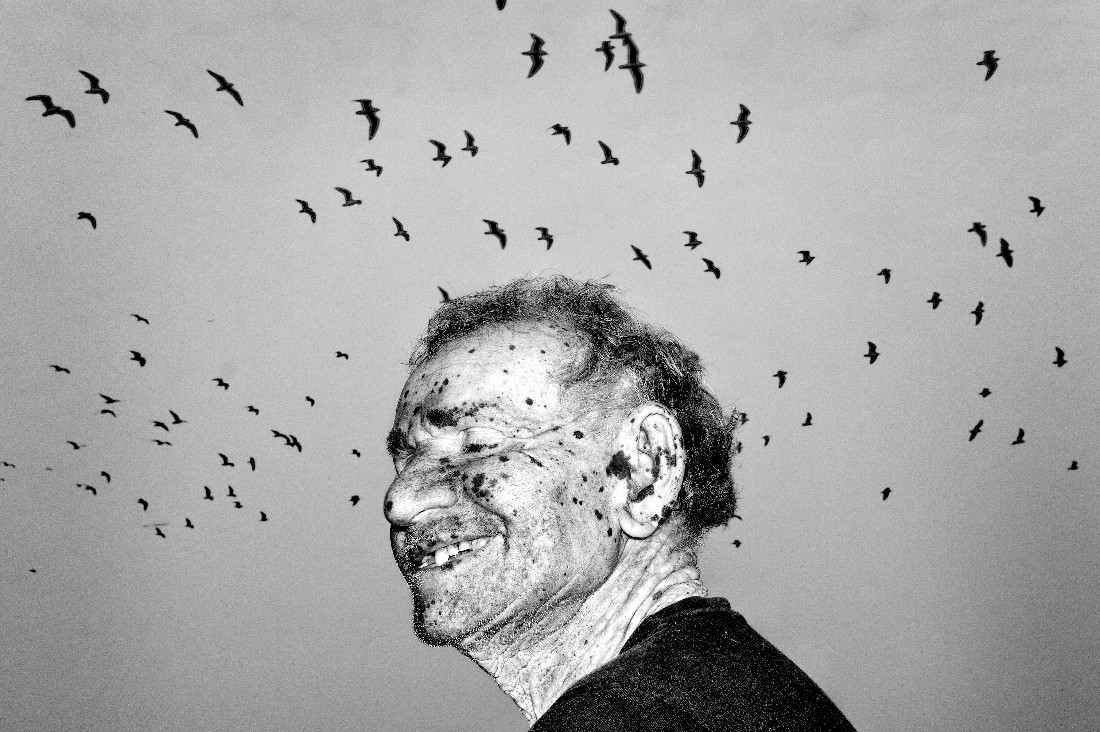 «Ο κόσμος μέσα μας», βραβείο «Black & White Street Photo of the Year 2021». Στη Γιαμούνα Γκατ, αποβάθρα στον ποταμό Γιαμούνα κοντά στο Νέο Δελχί όπου οι συγγενείς σκορπίζουν τις στάχτες των νεκρών τους, ο φωτογράφος είδε ξαφνικά έναν άντρα με πολλά μαύρα στίγματα στο πρόσωπο ενώ από πάνω του πετούσαν γλάροι, και απαθανάτισε τη στιγμή.