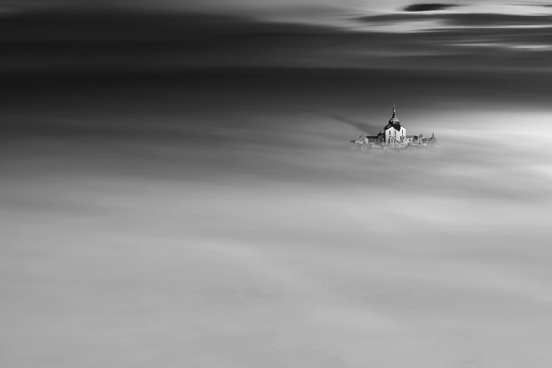 «Πνιγμένη στην ομίχλη», βραβείο «Black & White Architectural Photo of the Year 2021». Αεροφωτογραφία του προσκυνηματικού ναού του Αγίου Γιαν Νιεπομούτσκι στη Ζέλενα Χόρα της Τσεχίας, που μόλις διακρίνεται μέσα από την ομίχλη. Εργο του ιδιοφυούς αρχιτέκτονα Γιαν Μπλάζεϊ Σαντινί-Αϊχλ, ο  ναός είναι πλέον μνημείο πολιτιστικής κληρονομιάς της UNESCO.