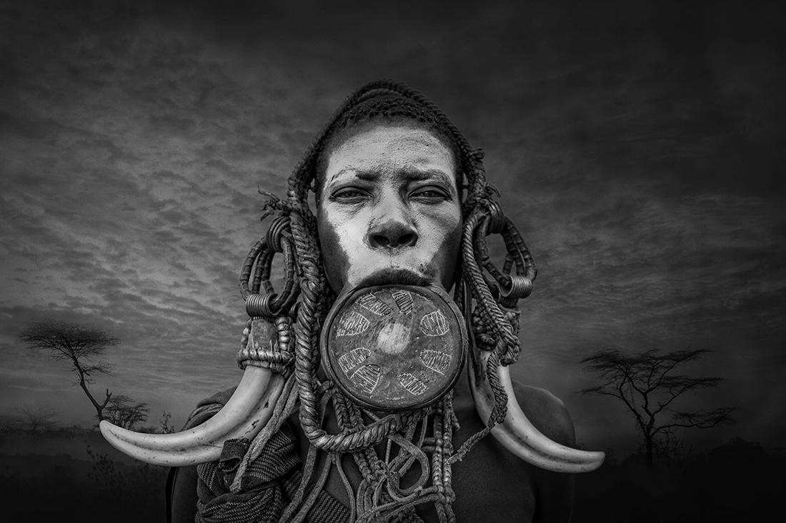 «Φυλή των Μούρσι», βραβείο «Black & White People Series of the Year 2021». Η φυλή των Μούρσι είναι απομονωμένη στην κοιλάδα Ομο στη Νότια Αιθιοπία κοντά στα σύνορα με το Σουδάν. Είναι μια από τις πιο συναρπαστικές φυλές της Αφρικής και η ζωή τους συνδυάζει τη βάναυση πραγματικότητα με την εκπληκτική ομορφιά.