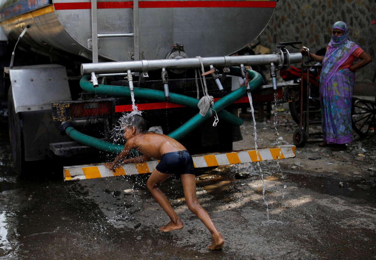 Το Νέο Δελχί κοχλάζει τον Ιούλιο, η αποφορά κόβει την ανάσα, αλλά η «μαρίδα» βρίσκει πάντα τον τρόπο να δροσίζεται ακολουθώντας το βυτιοφόρο του δήμου