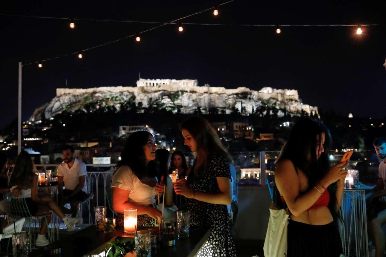 Νυχτερινό καρέ με φόντο την Ακρόπολη και θέμα νεαρόκοσμο της Αθήνας που διασκεδάζει σε κάποια ταράτσα-μπαρ