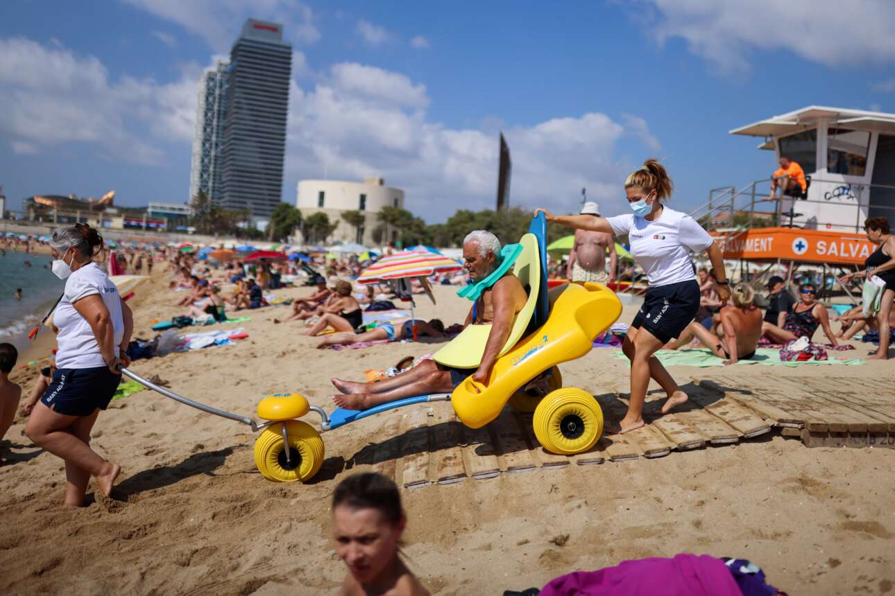 Θείος μεσογειακός Ιούλιος, για όλους μας: ο ηλικιωμένος με τα κινητικά προβλήματα ετοιμάζεται να βουτήξει σε κάποια παραλία της Βαρκελώνης μαζί με το κατάλληλο για μπάνιο αμαξίδιό του, υποβοηθούμενος από δύο ναυαγοσώστριες
