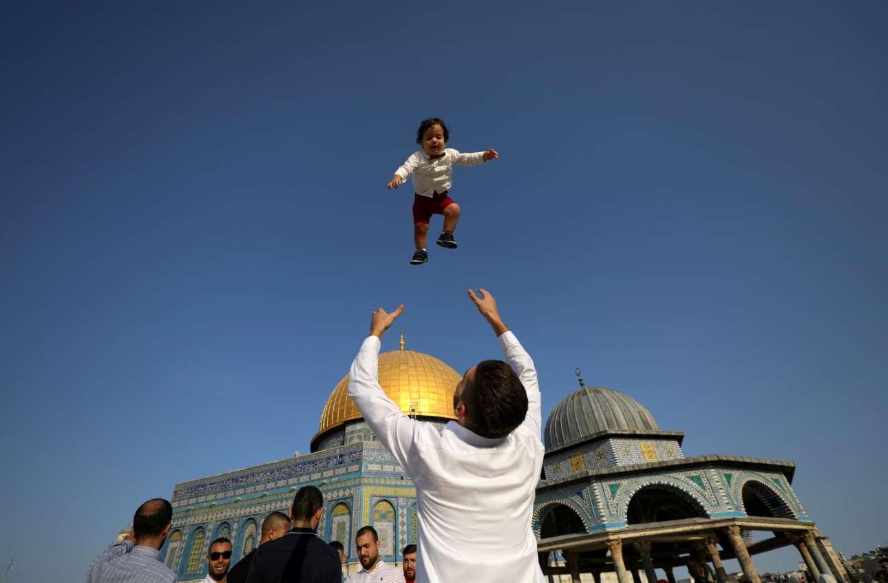 Αυτός ο Παλαιστίνιος παίζει με το παιδί του γιορτάζοντας την πρώτη ημέρα της ισλαμικής γιορτής Εϊντ αλ-Αντχα, την οποία οι Τούρκοι αποκαλούν Κουρμπάν Μπαϊράμι, στην παλιά πόλη της Ιερουσαλήμ