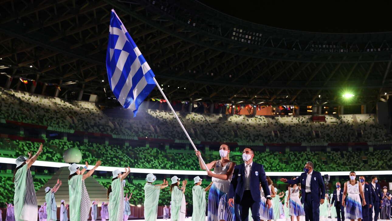 Αννα Κορακάκη και Λευτέρης Πετρούνιας μπαίνουν πρώτοι στο Ολυμπιακό Στάδιο του Τόκιο. Για πρώτη φορά οι διοργανωτές ζήτησαν τη σημαία των ομάδων να την κρατούν μαζί μια γυναίκα και ένας άνδρας αθλητής