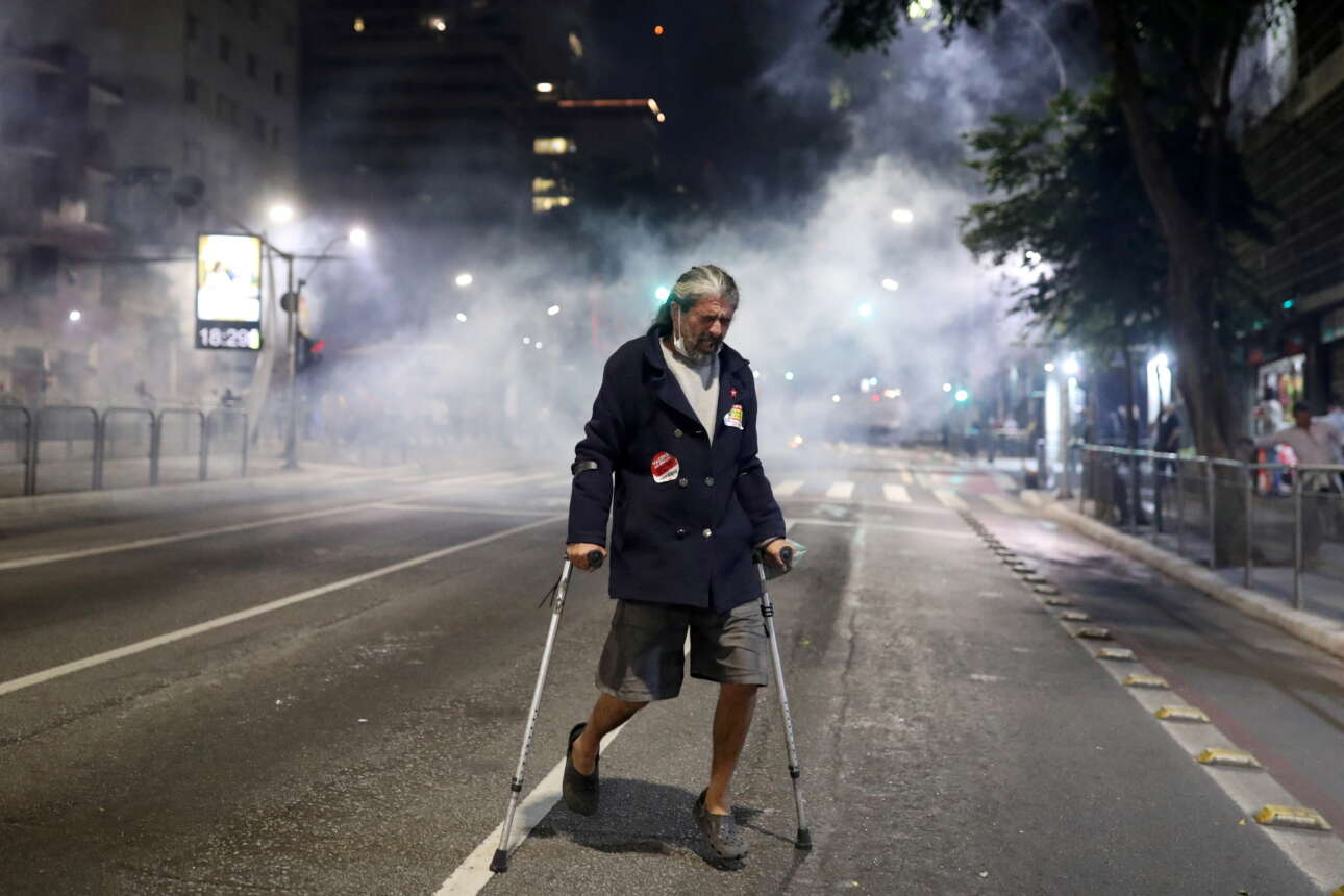 Σάββατο, 24 Ιουλίου. Ένας άνδρας με πατερίτσες, απομακρύνεται όσο πιο γρήγορα μπορεί, καθώς τα χημικά των δυνάμεων καταστολής κάνουν πνιγηρή την ατμόσφαιρα στο κέντρο του Σάο Πάολο. Η διαδήλωση χιλιάδων Βραζιλιάνων κατά του προέδρου Ζαΐχ Μπολσονάρο για το πώς (δεν) αντιμετώπισε την πανδημία της Covid-19 ήταν επεισοδιακή