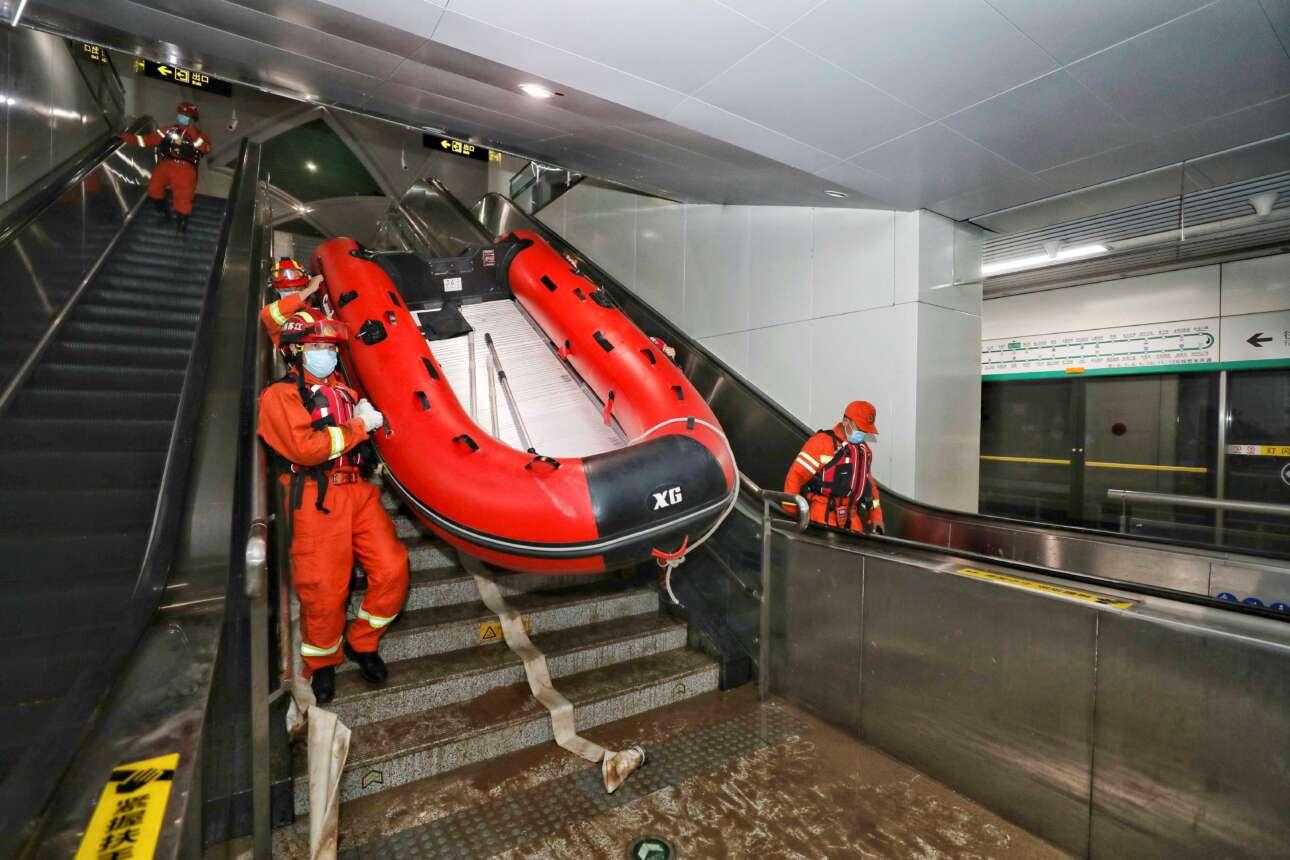 Κίνα. Διασώστες κατεβάζουν βάρκα στο πλημμυρισμένο μετρό της πόλης Σενγκτζού. Η καταστροφή εκεί προήλθε από έντονες βροχοπτώσεις