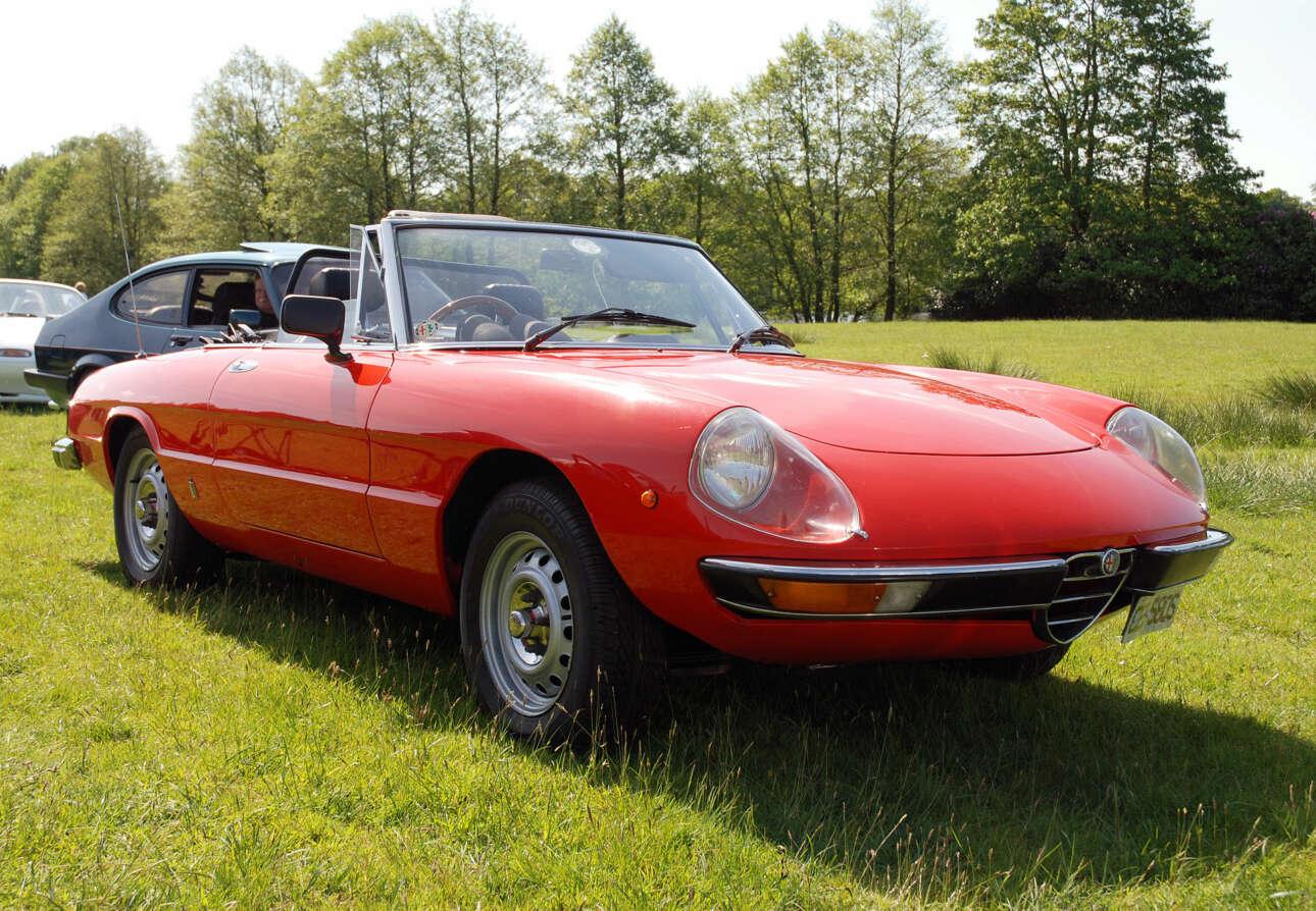 Alfa Romeo Spider (1966) H Alfa Romeo Spider δεν ήταν υπερβατική όπως μία Ferrari ή μία Jaguar E-Type. Ήταν, όμως, η πιο όμορφη Alfa Romeo της εποχής, η κούκλα της διπλανής πόρτας. Αυτό την έκανε στα μάτια μας πιο ποθητή καθώς όσοι την προλάβαμε φανταζόμασταν ότι, κάποτε, ίσως, πού ξέρεις, μπορεί και να την αποκτούσαμε. Ακόμα και οι χίπις στάθηκαν στις μύτες των ποδιών τους, το 1966, για να τη δουν όταν παρουσιάστηκε στη Διεθνή Έκθεση της Γενεύης.Η Alfa Romeo Spider ήταν ζωγραφισμένη από την ίδια πένα και έμελλε να μείνει στην ιστορία ως η πιο αειθαλής Alfa Romeo πουδιατηρήθηκε πεισματικά στην παραγωγή για 27 ολόκληρα χρόνια. Ακούγεται σαν αιώνας με τα σημερινά ήθη της αυτοκίνησης που στην τριετία αναζητάς το «φέις λιφτ». Με το που έμπαινες μέσα στη Spider αντίκριζες το χαρακτηριστικόχωστό τιμόνι – σήμα κατατεθέν της Alfa Romeo για πολλά χρόνια. Ήταν στιλπνό στην υφή, μετέδιδε στις απολήξεις των δακτύλων σου ένα ελαφρύ συντονισμό κάθε φορά που μάρσαρες ενώ ο κινητήρας κουνιόταν ελαφριά στις βάσεις του και, εν κινήσει, ήταν εξαιρετικά λαλίστατο. Καταλάβαινες με ακρίβεια χιλιοστού αν το κέρμα που μόλις πέρασες από πάνω του στο δρόμο ήταν κορώνα ή γράμματα. Με αυτό το αυτοκίνητο διάλεξε ο ηθοποιός Ντάστι Χόφμαν να αποπλανηθεί από την Αν Μπάνκροφτ στην ταινία «Ο πρωτάρης» (The Graduate, 1967). Ήταν, αν δεν με απατά η μνήμη μου, και ένα από τα τελευταία Alfa Romeo που εισήχθησαν στην αγορά των Η.Π.Α.
