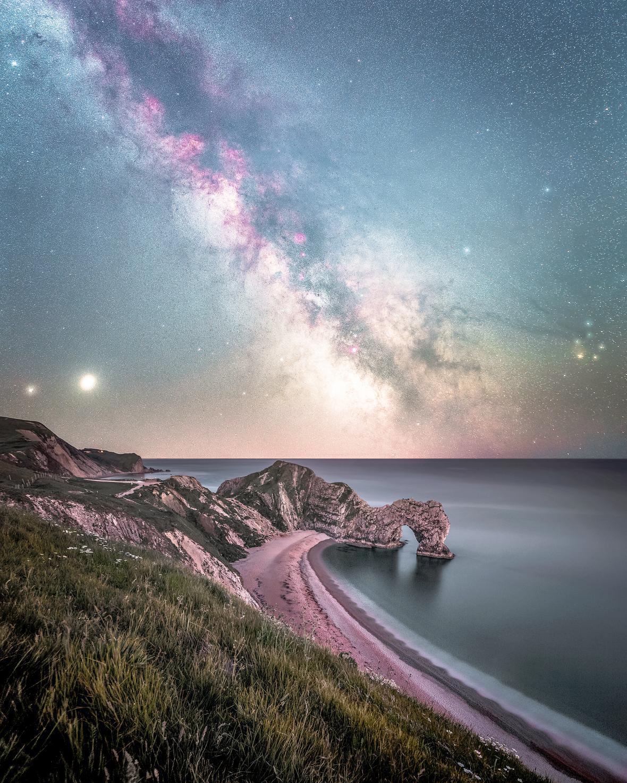 Οι γαλαξιακές δομές κυριαρχούν στον ουρανό μιας ακτής στην περιοχή Ντόρσετ στην νοτιοδυτική Αγγλία ενώ κάτω αριστερά τα δύο φωτεινά αντικείμενα είναι ο Κρόνος και ο Δίας