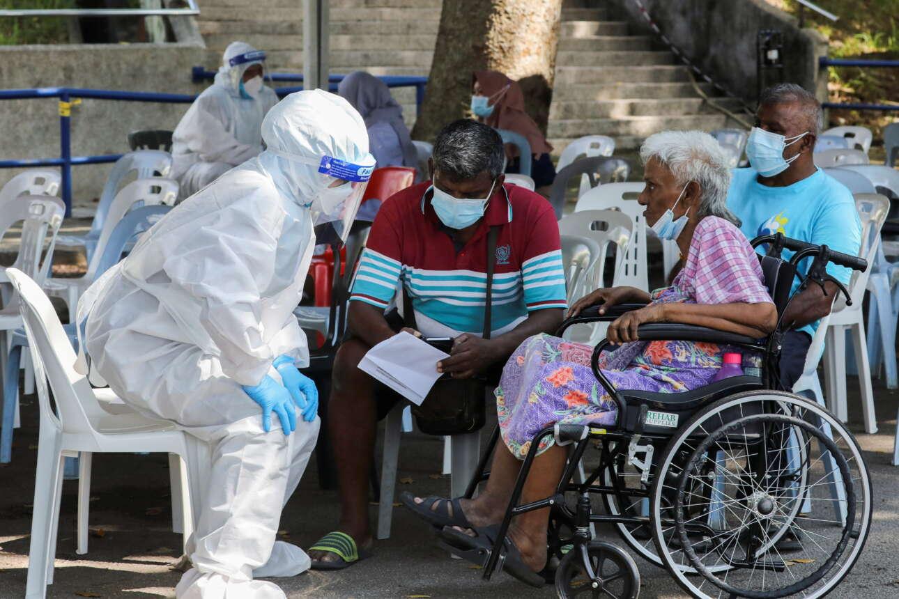 Νοσηλευτής με προστατευτικό εξοπλισμό μιλάει με μία ηλικιωμένη έξω από κέντρο υγείας για ασθενείς με κορονοϊό, στο Σα Αλάμ της Μαλαισίας