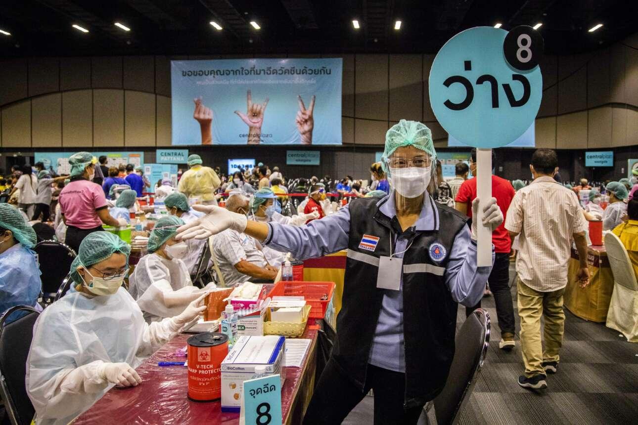 Εθελόντρια νοσοκόμα καλεί τον επόμενο ασθενή για να κάνει το εμβόλιο της Pfizer στο εμπορικό κέντρο Westgate στην Μπανγκόκ της Ταϊλάνδης