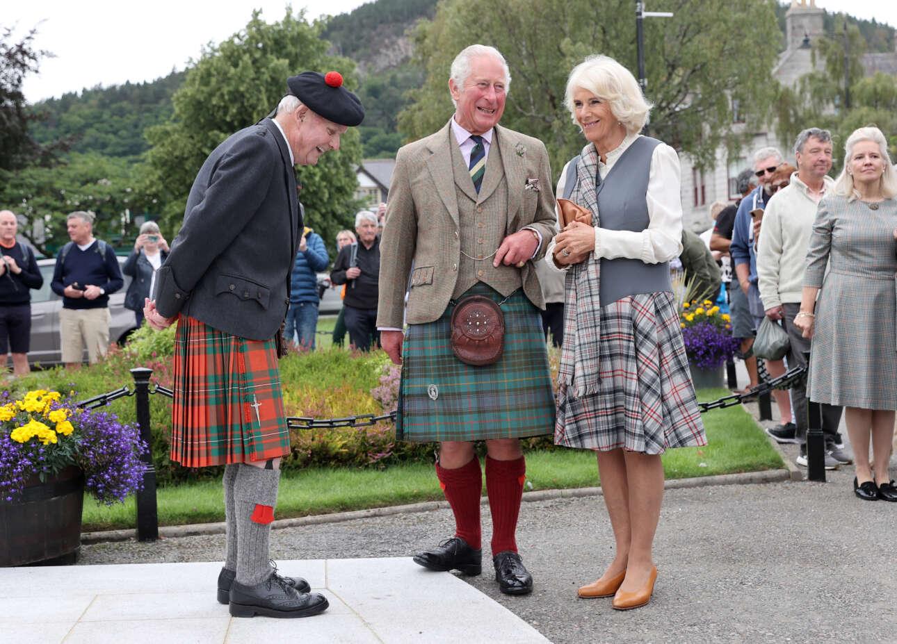 Ο πρίγκιπας Κάρολος της Ουαλίας ντυμένος με την παραδοσιακή φορεσιά και η δούκισσα της Κορνουάλης Καμίλα, μιλούν με τον 90χρονο Χιού Ινκστερ κατά την επίσκεψή τους στο χωριό Μπάλατερ της Σκωτίας