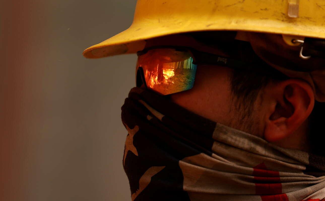 Η πυρκαγιά αντανακλάται στα γυαλιά του πυροσβέστη στο μέτωπο της πυρκαγιάς