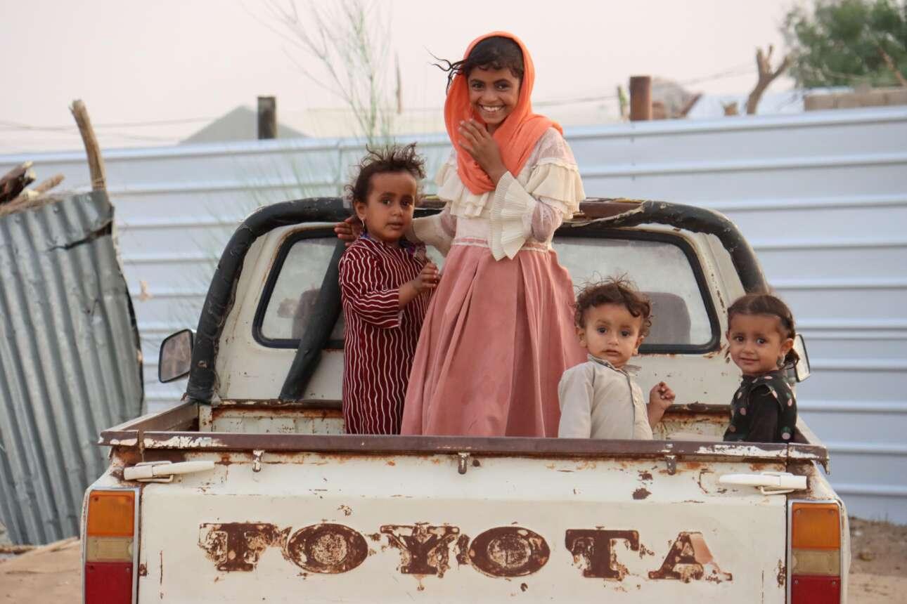 Πονεμένα πιτσιρίκια, άλλα χαμογελαστά και άλλα έκπληκτα, ενδίδουν στα παρακάλια του φωτογράφου και του χαρίζουν ένα καλό καρέ από την καρότσα του ταλαιπωρημένου αγροτικού. Το περιστατικό στην Υεμένη, σε ένα στρατόπεδο ξεσπιτωμένων οικογενειών που προς το παρόν ειρηνεύει