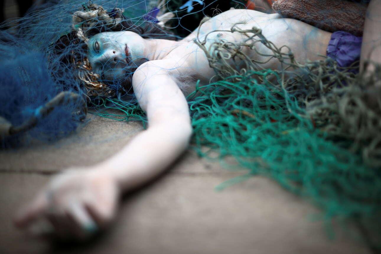 Κέντρο Λονδίνου. Οταν η θάλασσα πεθαίνει, πεθαίνουμε και εμείς λέει η οργάνωση Ocean Rebellion, έτσι η κοπέλα που βλέπετε «απεβίωσε» σε οικολογικό χάπενινγκ πιάνοντας μούχλα μέχρι τις τρίχες της μασχάλης. Με το ολοζώντανο «Δελφινοκόριτσο» του Ελύτη, δυστυχώς, καμία σχέση. Θα φταίει η έλλειψη Σαρωνικού…
