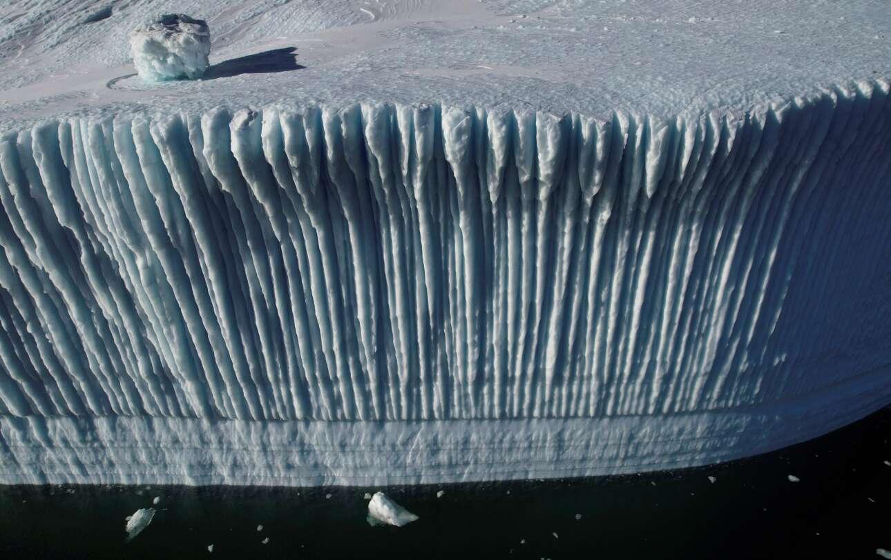 Γροιλανδία. Υπέροχο φυσικό γλυπτό έχει σχηματίσει η φύση στην άκρη του παγόβουνου. Πολύπτυχο, με ιδανικές φωτοσκιάσεις και δυνητικώς απειλητικό, καθώς ο φακός πέτυχε να το δείξει επιτιθέμενο στο μάτι μας και στην ψυχή μας