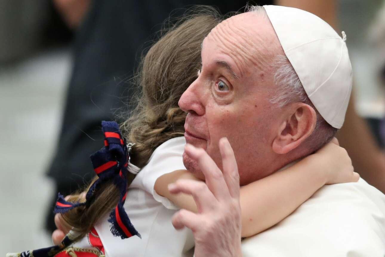 Αυθορμήτως ή όχι και τόσο, το παιδί όρμησε στην αγκαλιά του πάπα. Το βλέμμα τού Φραγκίσκου δείχνει πόσο εξεπλάγη από την κίνηση της μικρής, ωστόσο ο φακός είναι παιχνιδιάρης και υπαινίσσεται ότι το κοριτσάκι κάτι εξωφρενικό τού ψιθυρίζει στο αυτί