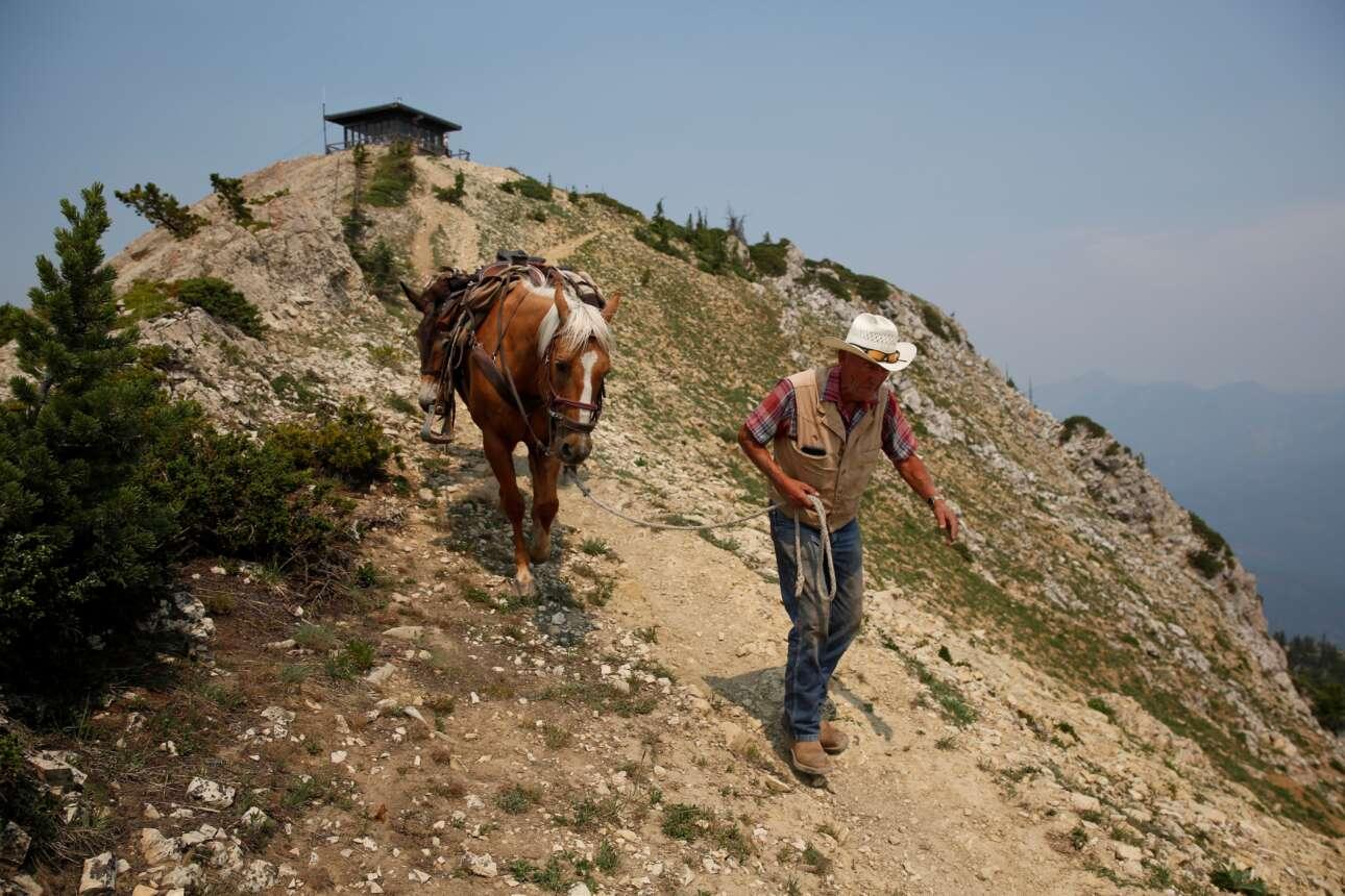 Ο 78χρονος Νόρμαν Κάμρουντ, οδηγεί το άλογό του στο βραχώδες μονοπάτι απομακρυνόμενος από το πυροφυλάκιο που βρίσκεται στην πόλη Αγκούστα της Μοντάνα. Χάρη σε αυτόν και τα τετράποδα ζώα του, η Σαμσάρα προμηθεύεται τα απαραίτητα για τη διαβίωσή της. Σύμφωνα με το ρεπορτάζ, τη δεκαετία του 1950, περίπου 5.000 πύργοι είχαν κατασκευαστεί σε όλες τις Ηνωμένες Πολιτείες. Πολλοί έκλεισαν έκτοτε, καθώς οι υπέρυθρες κάμερες και τα drones αντικαθιστούν το ανθρώπινο μάτι. Η Ενωση Δασικών Πυρκαγιών εκτιμά ότι σήμερα εξακολουθούν να λειτουργούν περίπου 400 πύργοι επιτήρησης...