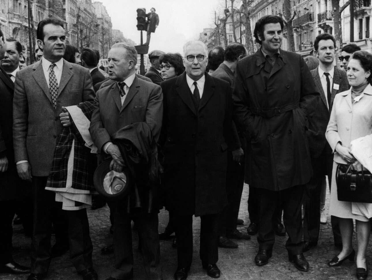 Πρωτομαγιά του 1970, ο Μίκης Θεοδωράκης στο Παρίσι στην πορεία του Κομμουνιστικού Κομματος Γαλλίας. Αριστερά στην εικόνα ο Ζορζ Μαρσέ, θρυλικός ηγέτης της γαλλικής Αριστεράς