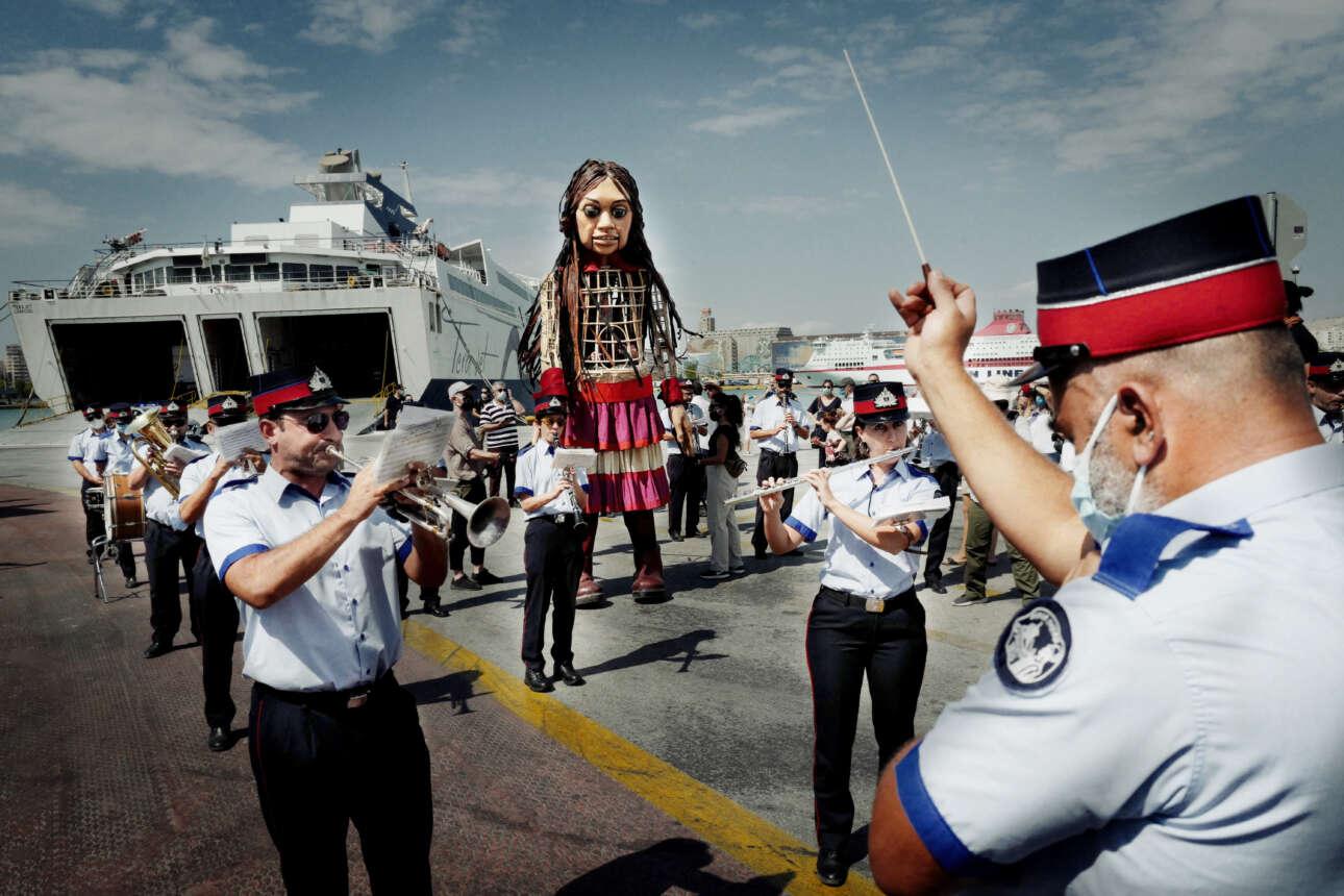Η ορχήστρα του δήμου Πειραιά συνοδεύει την ξύλινη κούκλα «Αμάλ», που συμβολίζει το ταξίδι των παιδιών που πλήττονται από την προσφυγική κρίση, καθώς αναχωρεί για την Ιταλία