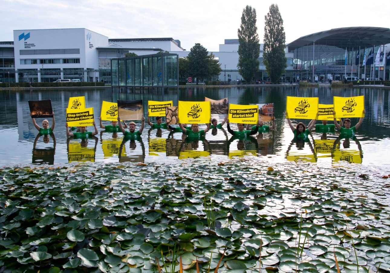 Αυτή η αμφίβια παρέα αποτελείται από μέλη της Greenpeace. Ολοι τους διαδηλώνουν και συγχρόνως δροσίζονται στο Μόναχο, στον προαύλιο χώρο της έκθεσης IAA MOBILITY 2021