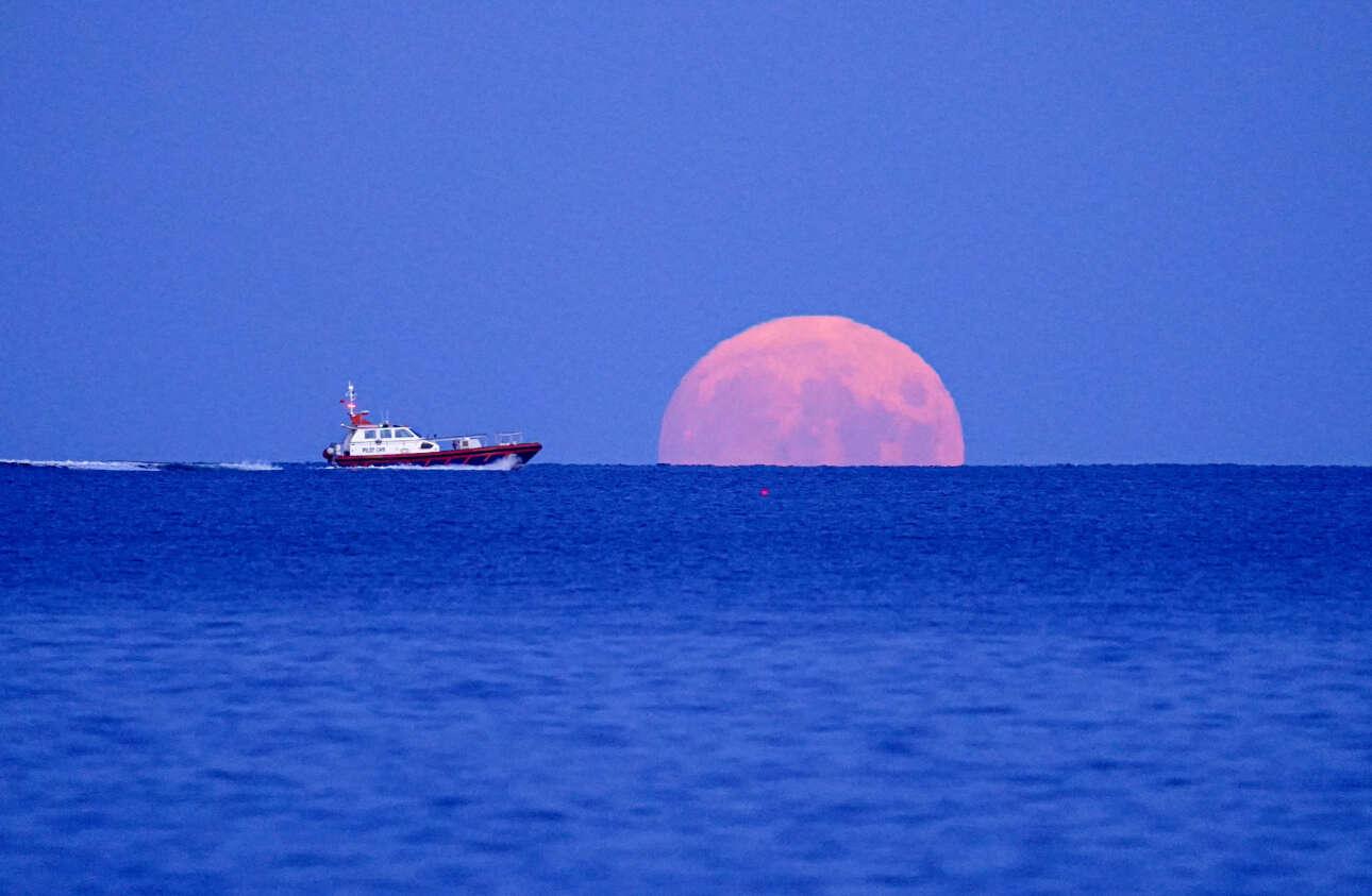 Βάρκα λίγα δεύτερα πριν «τεμαχίσει» το ολόγιομο φεγγάρι στην παραλία Σουάνπουλ στο Φάλμουθ της Αγγλίας