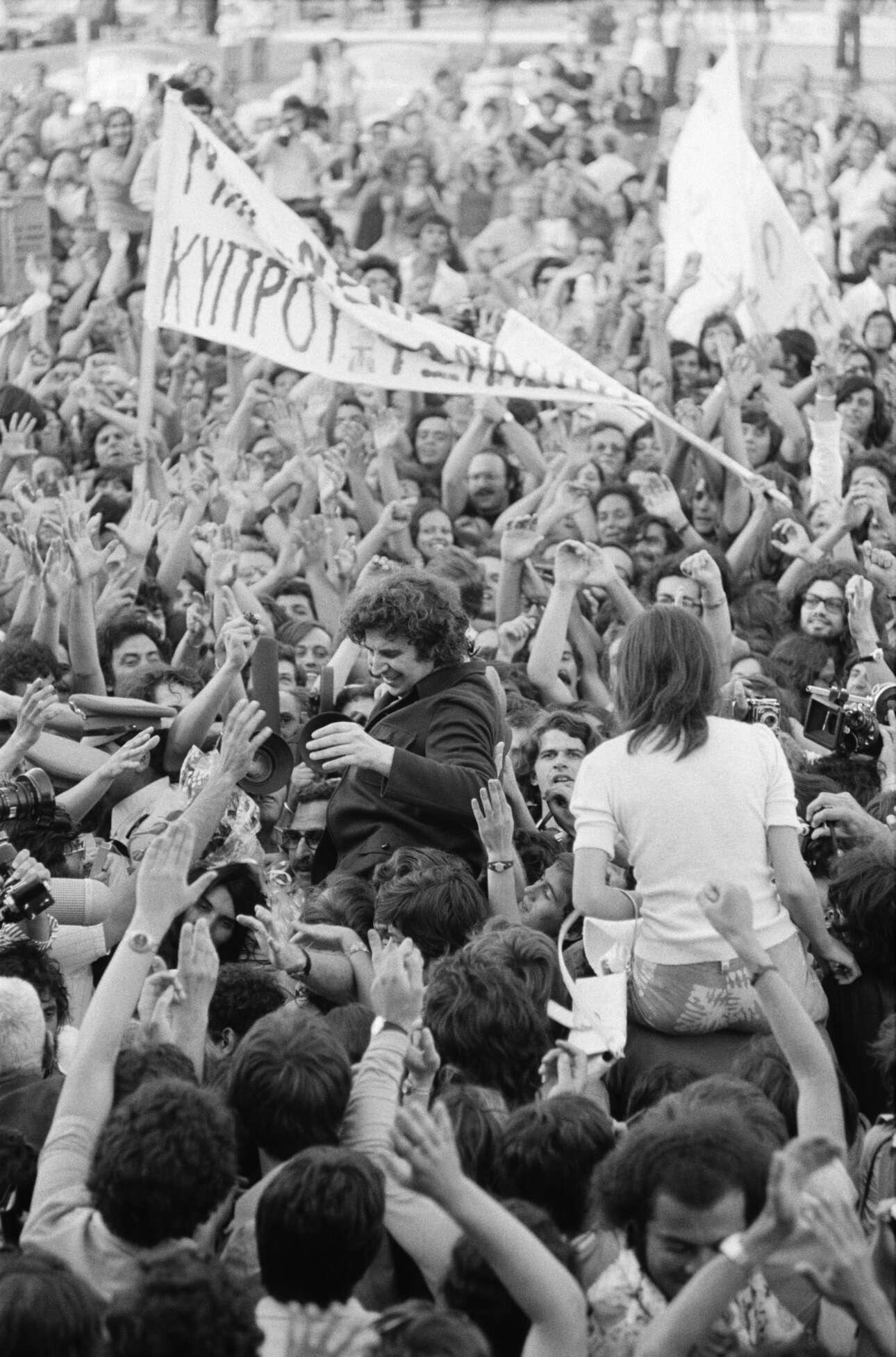 Ιούλιος του 1974, ο Μίκης υψώνεται στα χέρια του λαού που έχει σπεύσει στο αεροδρόμιο για να τον καλωσορίσει